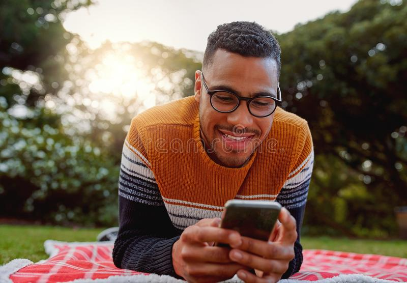 Portrait of an african smiling young man student wearing black eyeglasses relaxing in park using smart phone - college royalty free stock photos
