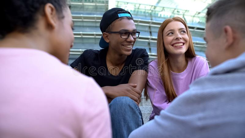 Smiling afro-american teenager looking at pretty female aside, communication. Stock photo stock image