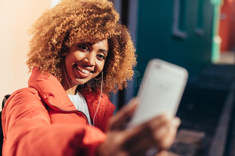 Smiling afro american tourist taking a selfie. Cheerful tourist woman on vacation taking a selfie using mobile phone standing outdoors. Portrait of a smiling royalty free stock photos