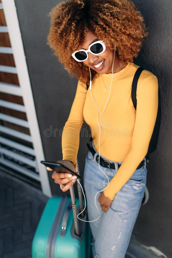 Woman traveller standing with luggage. Smiling afro american tourist woman standing with her luggage holding a mobile phone in hand. Cheerful woman traveller in stock images