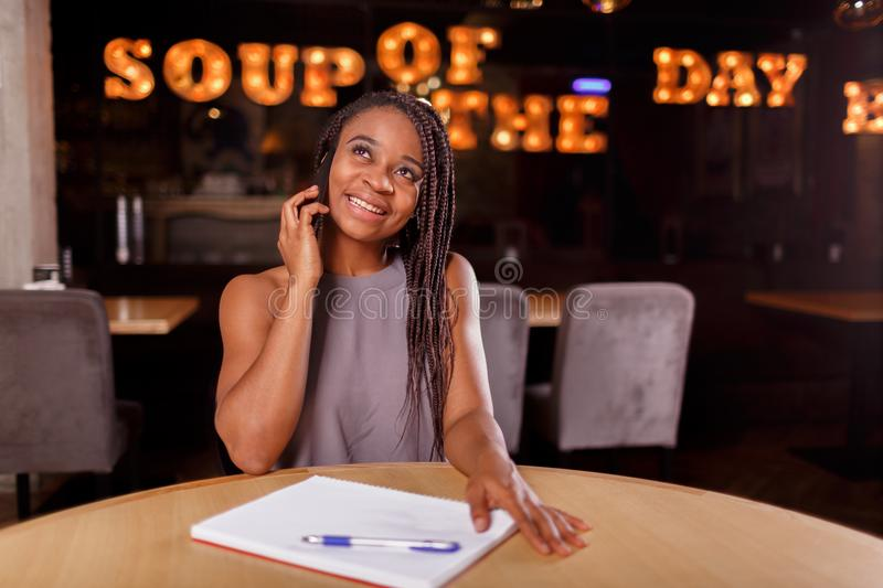 A smiling Afro-American woman is working stock images
