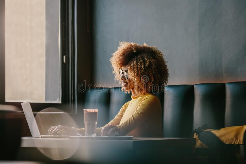 Smiling afro american woman sitting at a cafe working on laptop royalty free stock photography
