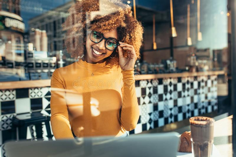 Smiling woman sitting at a cafe looking at laptop royalty free stock photography