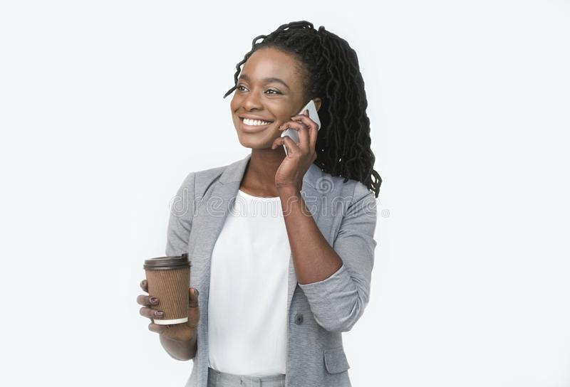 Smiling Afro Businesswoman Talking On Cellphone Holding Coffee Cup, White Background stock photography