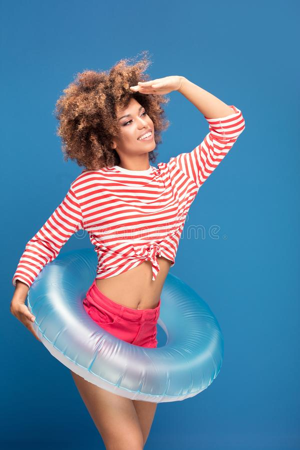Smiling afro woman in sailor style shirt. Smiling african american woman posing on blue background, wearing shirt in white and red stripes, holding inflatable royalty free stock images