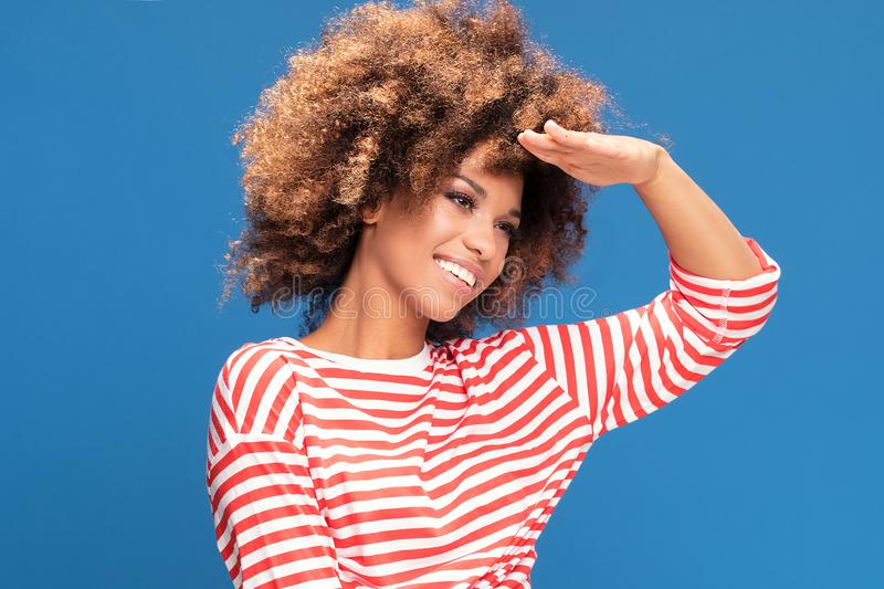Smiling afro woman in sailor style shirt. Portrait of smiling african american woman posing on blue background, wearing shirt in white and red stripes, sailor royalty free stock photography