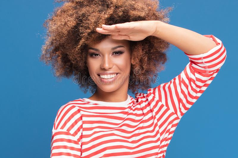 Smiling afro woman in sailor style shirt. Portrait of smiling african american woman posing on blue background, wearing shirt in white and red stripes, sailor royalty free stock images