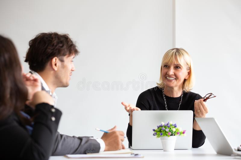 Smiling aged business woman talking and looking at colleague while team meeting, Happy attentive female team leader. Smiling aged business women talking and stock image
