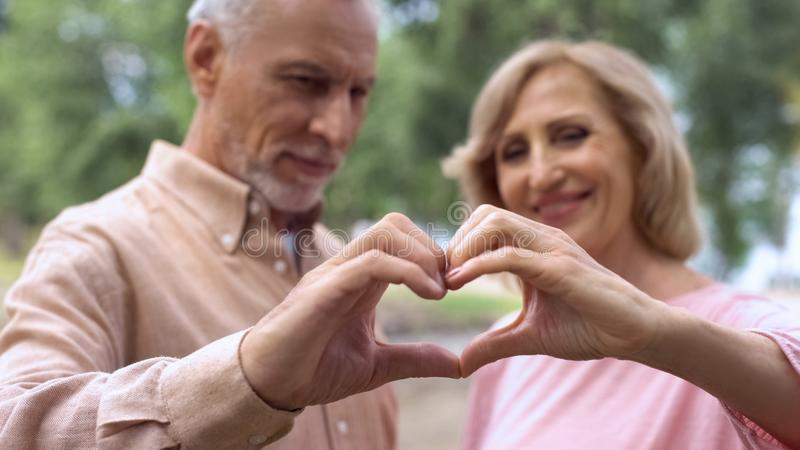 Smiling aged couple showing heart sign, love symbol, happy marriage, affection stock photo