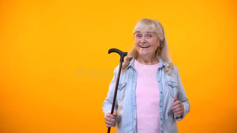 Smiling aged lady holding walking stick, equipment for disabled or elderly stock image