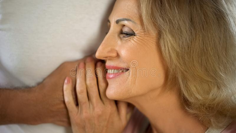 Smiling aged lady leaning on husband hand, happy married couple, affection royalty free stock images