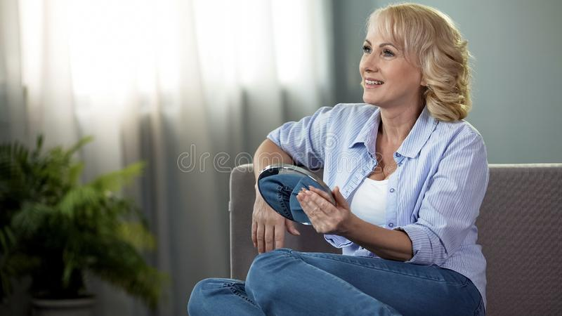 Smiling aged lady sitting sofa with hand mirror, female skin care, cosmetology royalty free stock image