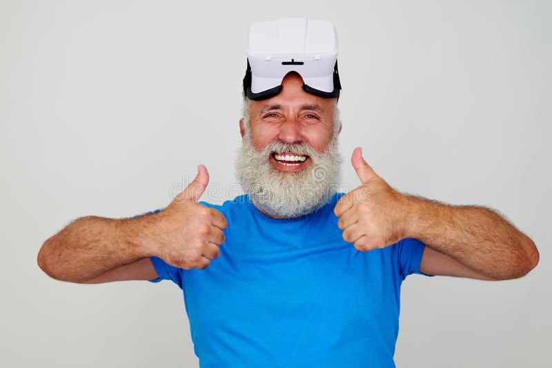 Smiling aged man in VR-headset on his head giving two thumbs up stock photos