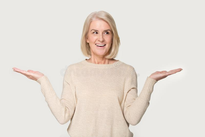 Smiling mature woman compare options considering pros and cons stock images