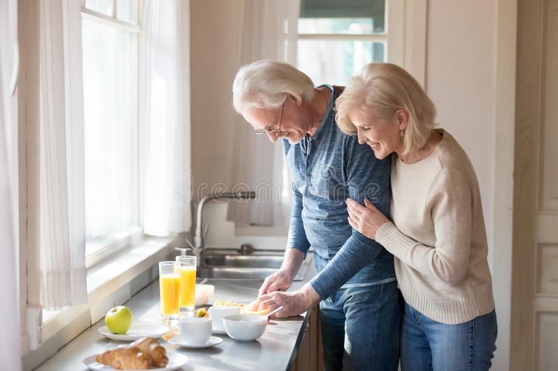 Happy aged woman embrace husband cooking healthy breakfast. Smiling aged wife hug men from behind watching him preparing healthy food, loving senior women stock photography