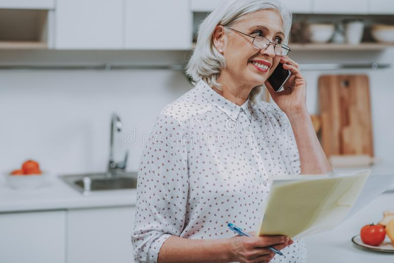 Smiling aged woman is communicating on phone at home stock image