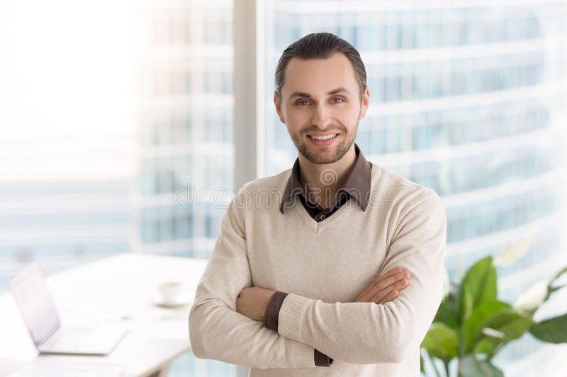Smiling ambitious young businessman standing in office with arms stock photo