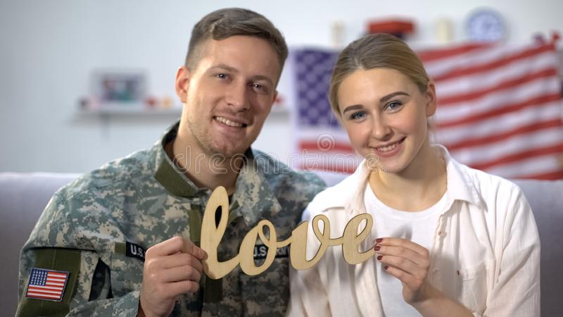 Smiling american soldier and his girlfriend showing wooden love sign on camera. Stock photo royalty free stock photos