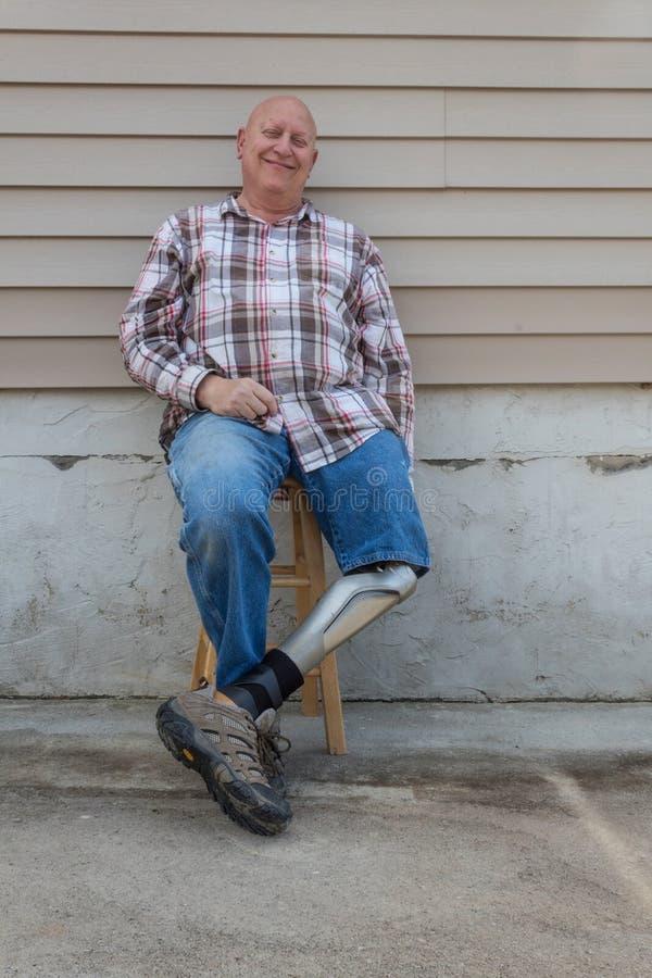 Smiling amputee man, prosthetic leg forward, seated royalty free stock photo
