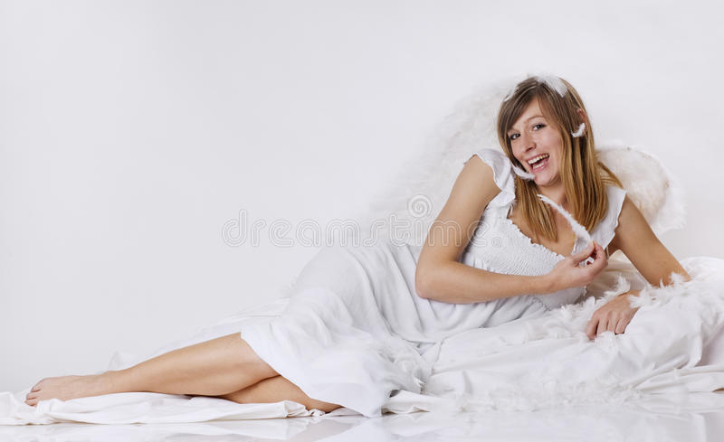 Smiling angel with a white dress and a feather stock images
