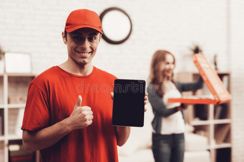 Smiling Arab Deliveryman with Tablet and Girl. Courier Delivery. Man Deliveryman with Tablet. Worker Man Arab Nationality. White Interior. Smiling Deliveryman royalty free stock photography