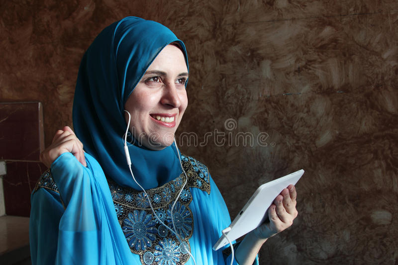 Smiling arab muslim woman listening to music. Photo of arabian egyptian muslim woman feeling happy while listening to music from her tablet through headset stock photos