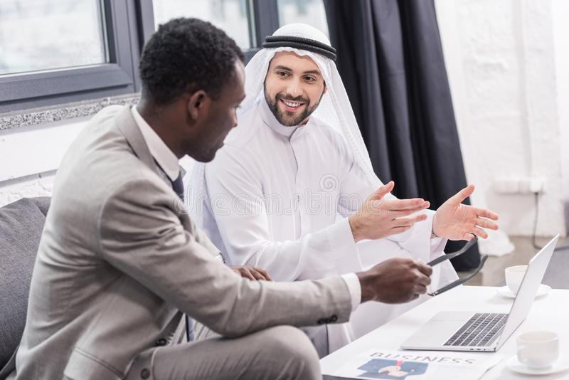 Smiling arabian businessman and african american partner talking. In office royalty free stock photo