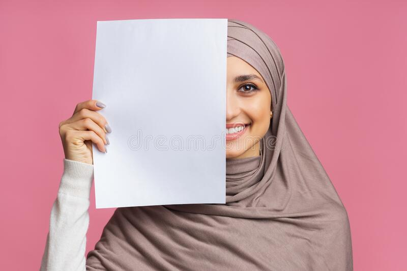 Smiling arabic girl covering half of face with blank paper sheet royalty free stock photo