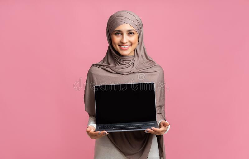 Smiling Arabic Girl In Hijab Holding Laptop Computer With Black Screen stock photo