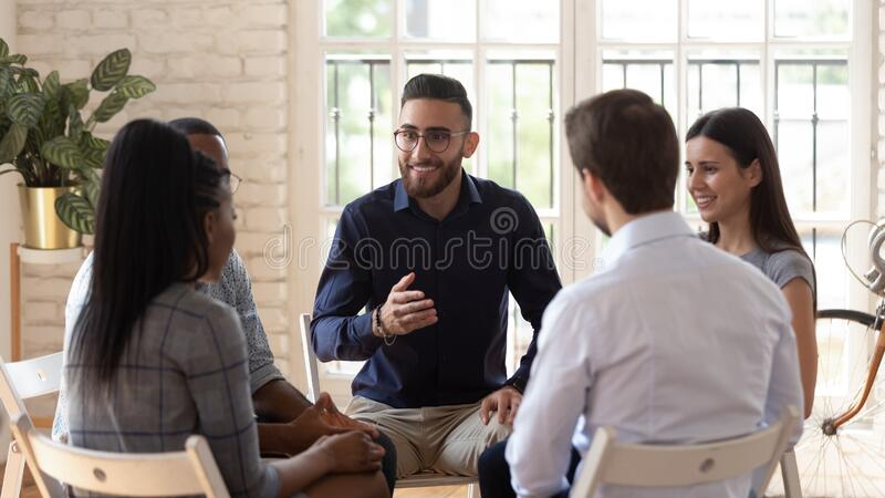 Diverse people speak share problems at therapy session. Smiling Arabic male mentor or coach sit in circle with diverse patients counseling help overcome life stock photos