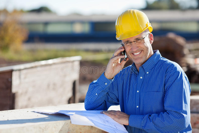 Smiling Architect Using Mobile Phone At Site stock images