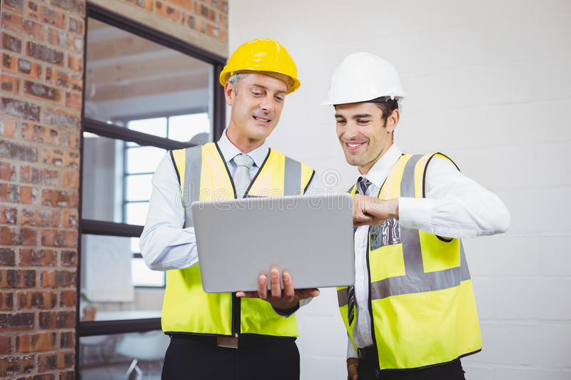 Smiling architects discussing while holding blueprint royalty free stock images