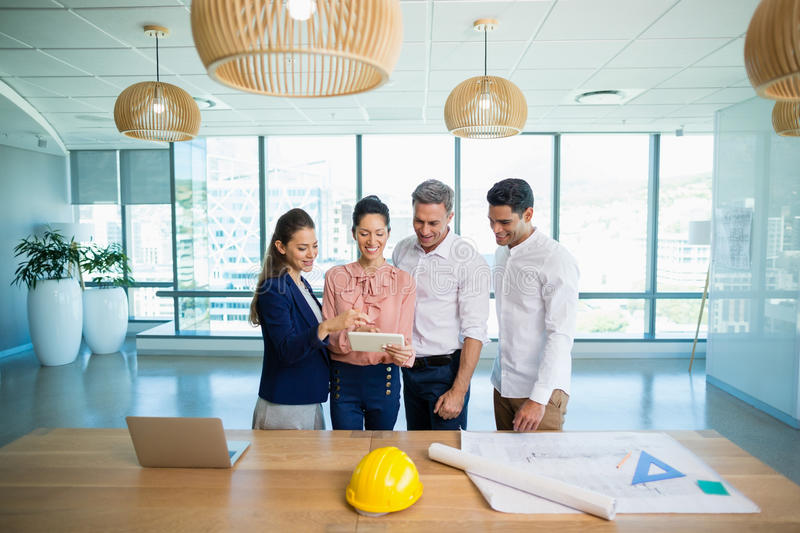 Smiling architects discussing over digital tablet stock image