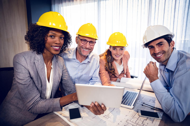 Smiling architects discussing over digital tablet in office royalty free stock photography