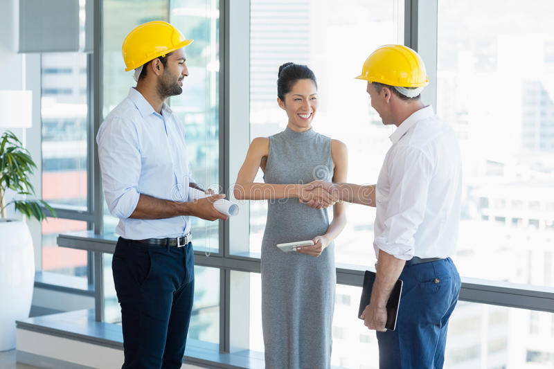Smiling architects shaking hands with each other royalty free stock photo