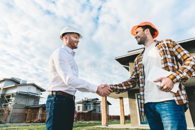 Smiling architects shaking hands in front of. Construction site stock photography