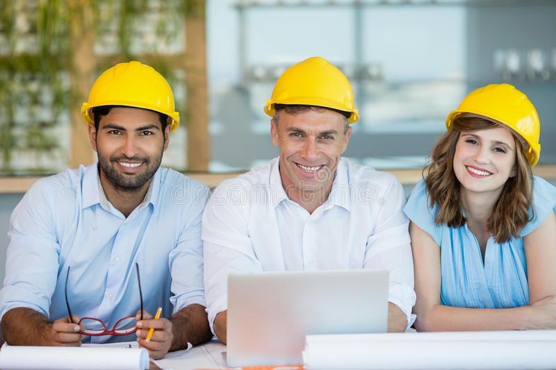 Smiling architects sitting together in conference room stock photos
