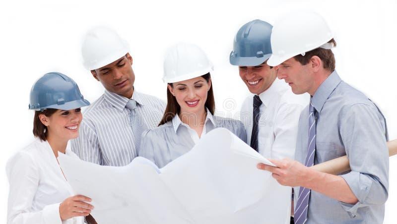Smiling architects studying a blueprint royalty free stock image