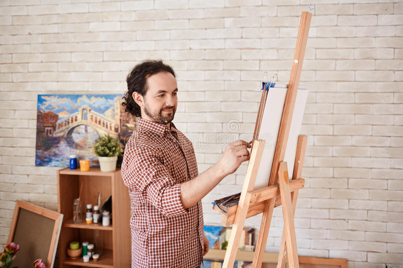 Smiling Artist Drawing Picture in Art Studio stock images