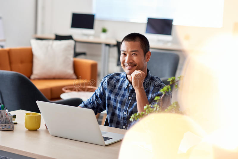 Smiling Asian architect at work in a modern office. Portrait of a young Asian architect smiling confidently while sitting alone at a desk in a modern office royalty free stock images
