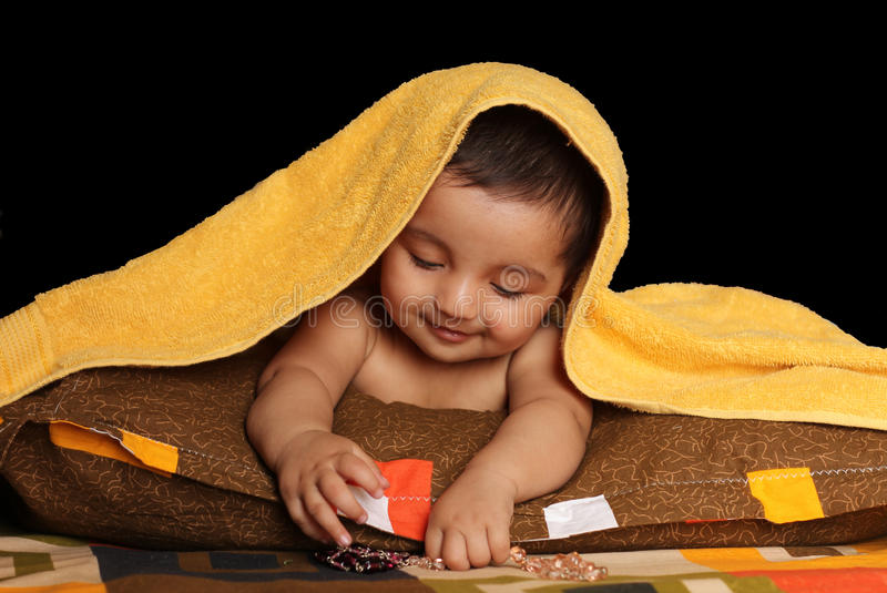 Smiling Asian baby girl under yellow towel royalty free stock image