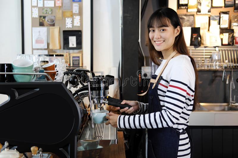 Smiling asian barista preparing cappuccino with coffee machine. royalty free stock photos