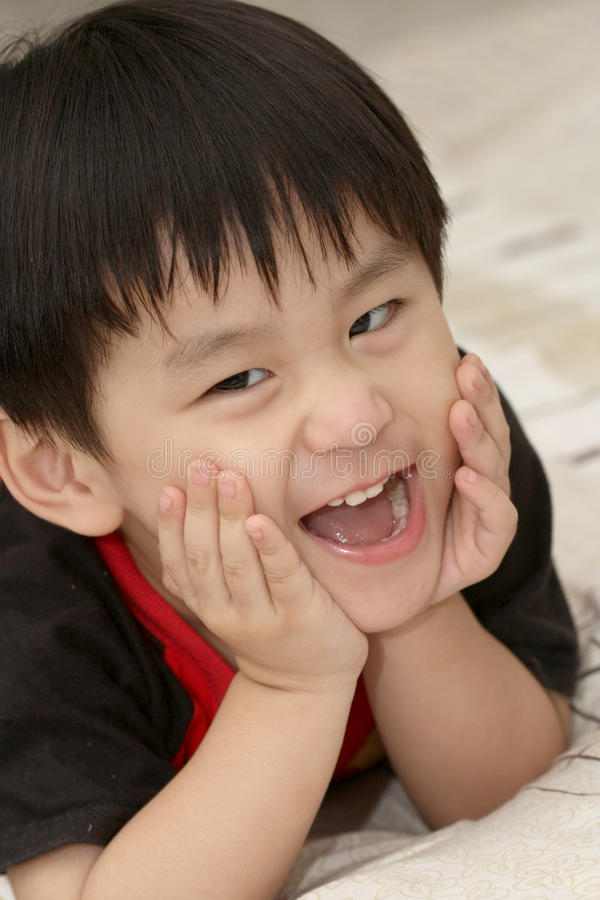 Smiling asian boy lying on bed