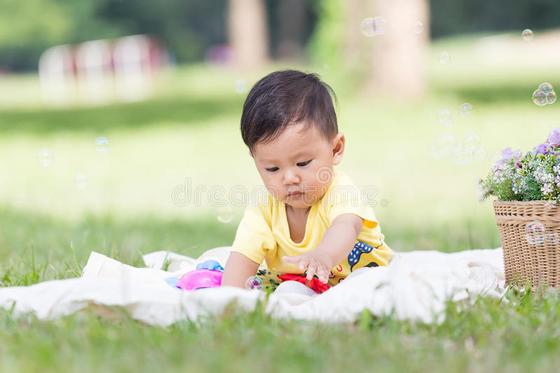 Smiling asian boy toddler sit on white Cotton in the green gras. Smiling asian boy black hair and eyes toddler sit on white Cotton in the green grass alone and stock image