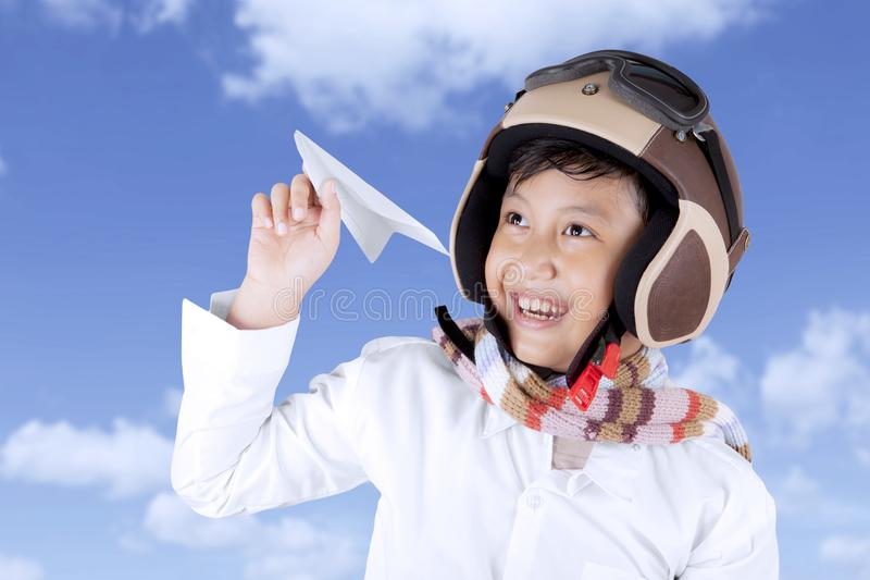 Smiling Asian boy wearing helmet holding a plane paper stock photo