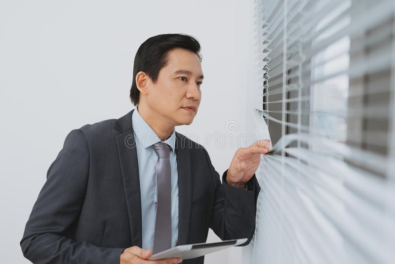 Smiling asian businesman holding digital tablet standing by the stock photography