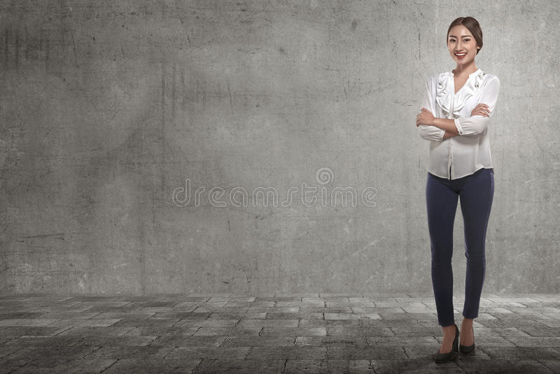 Smiling asian business woman with folded arms in the street. Against grey wall background stock photos