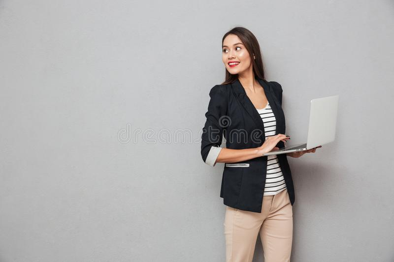 Smiling asian business woman holding laptop computer and looking back. Over gray background stock photography