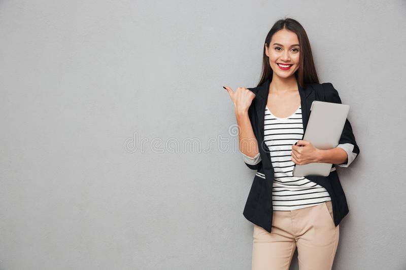 Smiling asian business woman holding laptop computer and pointing away stock images