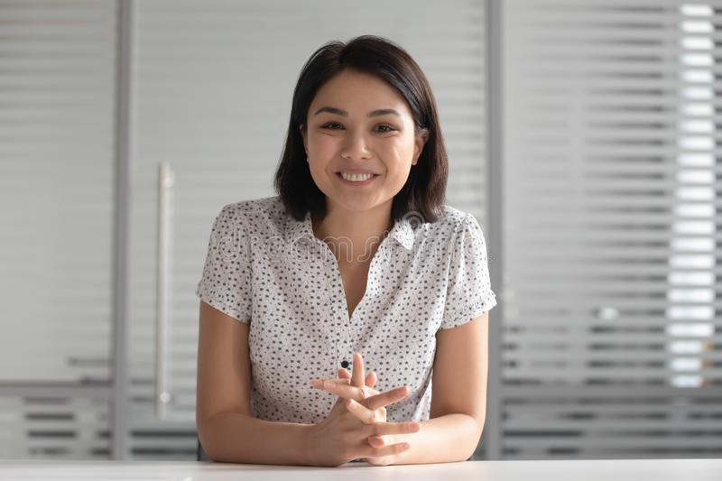Smiling asian business woman looking at camera shooting video training royalty free stock image